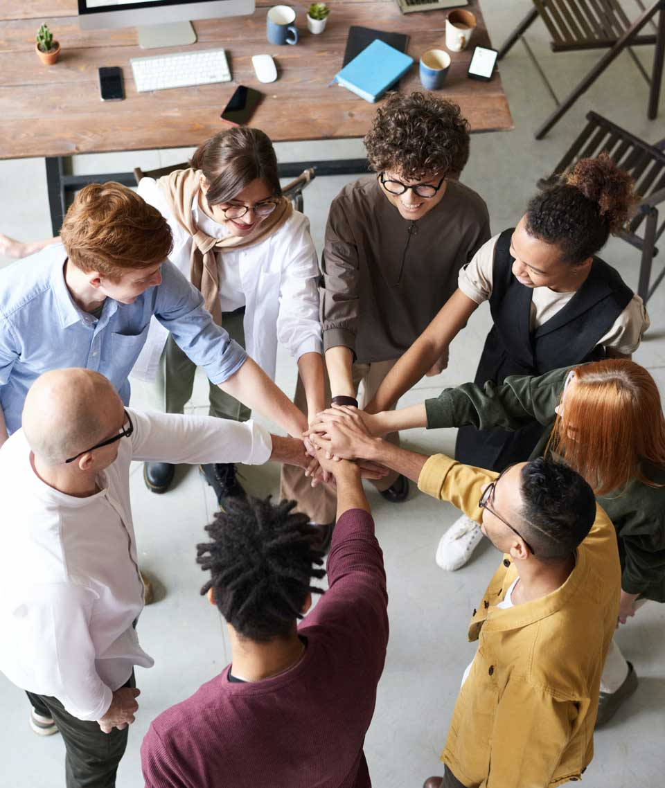 Group of young co-workers with hands together